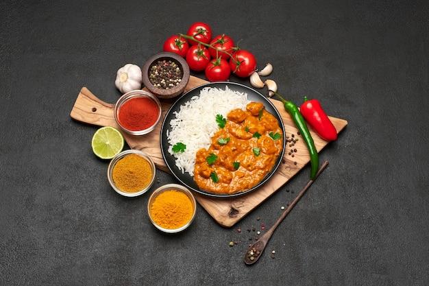 Piatto di riso al curry di pollo tradizionale e spezie sul tavolo scuro