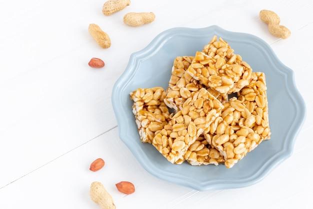 Piatto di pezzi di caramelle fragili di arachidi tradizionali. dolci su uno sfondo bianco di legno.