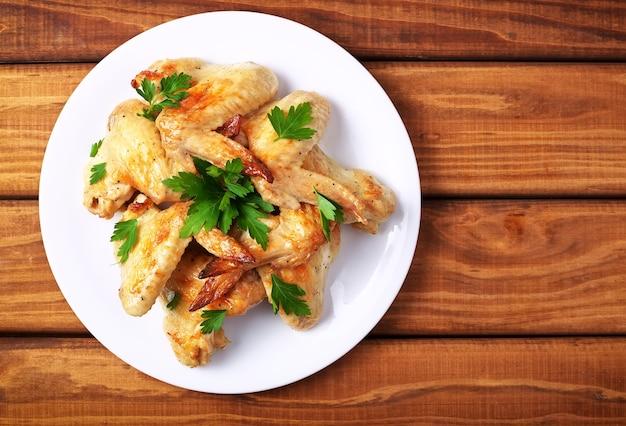 Piatto con ali di pollo al forno e prezzemolo su uno sfondo di legno. vista dall'alto
