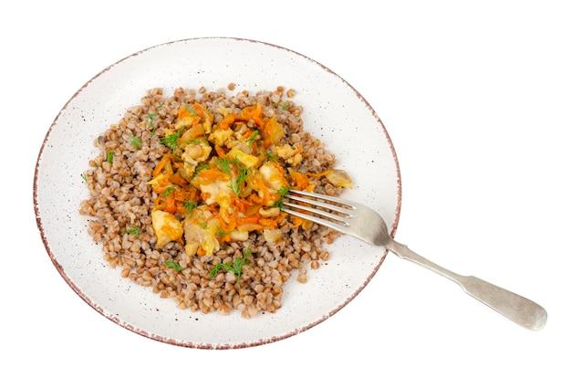 Piastra con porridge di grano saraceno con verdure e pollo isolato su sfondo bianco. foto di studio