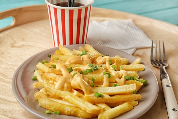 Piatto con patatine al formaggio e tazza di soda sul vassoio