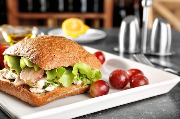 Piatto con insalata di pollo in panino con hamburger sul tavolo