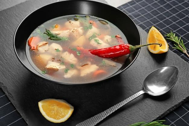 Piatto con zuppa di pollo e peperoncino sul tavolo