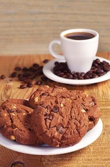 Piastra con biscotti al cioccolato e tazza di caffè caldo sulla tavola di legno d'epoca