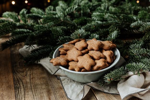 Un piatto con i biscotti su uno sfondo di rami di abete.