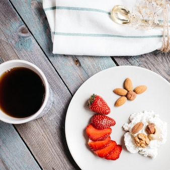 Zolla con la ricotta, le fragole e le noci, una tazza di caffè e gli asciugamani sulla tavola di legno, alimento sano, prima colazione