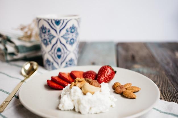 Zolla con la ricotta, le fragole e le noci, una tazza di caffè e gli asciugamani sulla tavola di legno, alimento sano, prima colazione Foto Premium