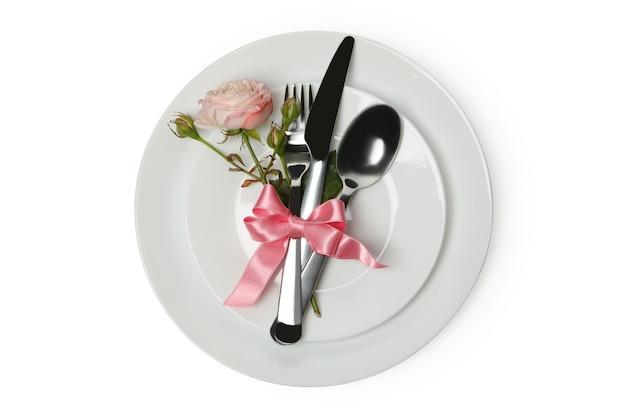 Piastra con posate, fiocco rosa e rosa isolato su sfondo bianco