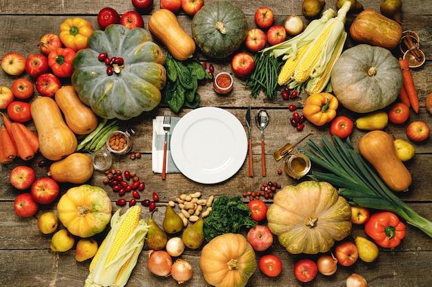 Piatto con posate circondato da assortimento di verdure su tavola di legno