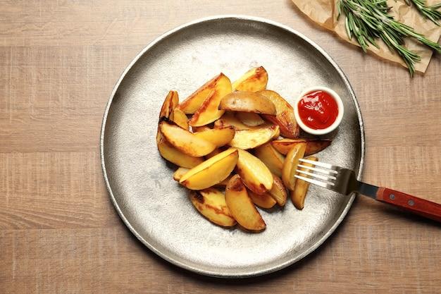 Piatto con deliziosi spicchi di patate al forno e salsa sul tavolo