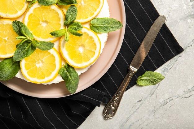 Piatto con deliziosa cheesecake e limoni sul tavolo