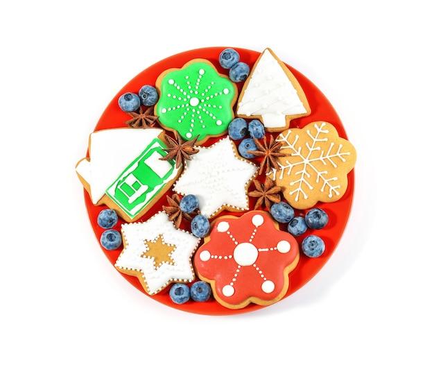 Piatto con deliziosi biscotti di natale su sfondo bianco