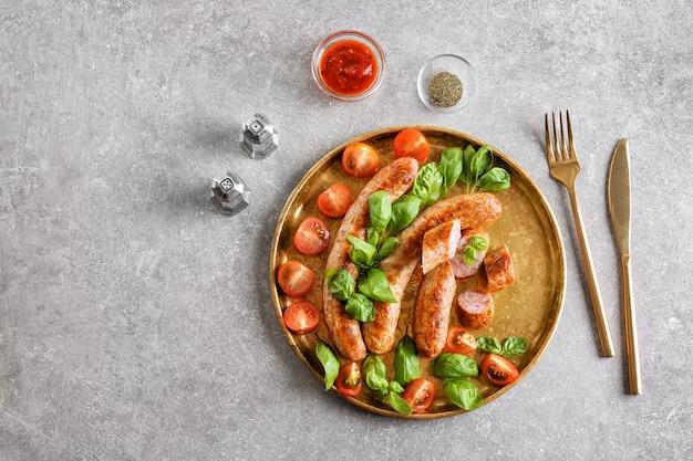 Piastra con deliziose salsicce alla griglia, pomodoro e basilico su sfondo grigio