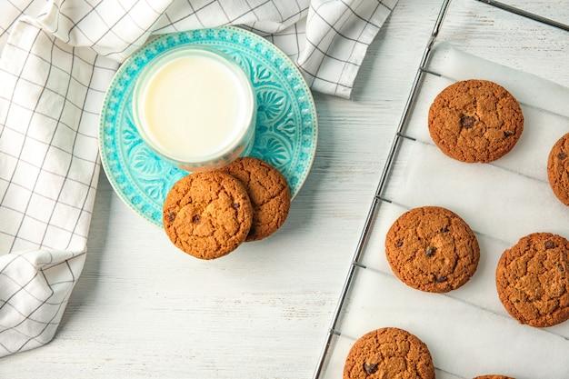 Piastra con deliziosi biscotti di farina d'avena e un bicchiere di latte sul tavolo