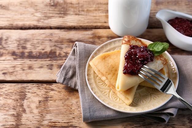 Piastra con deliziose frittelle e marmellata di frutti di bosco sul tavolo