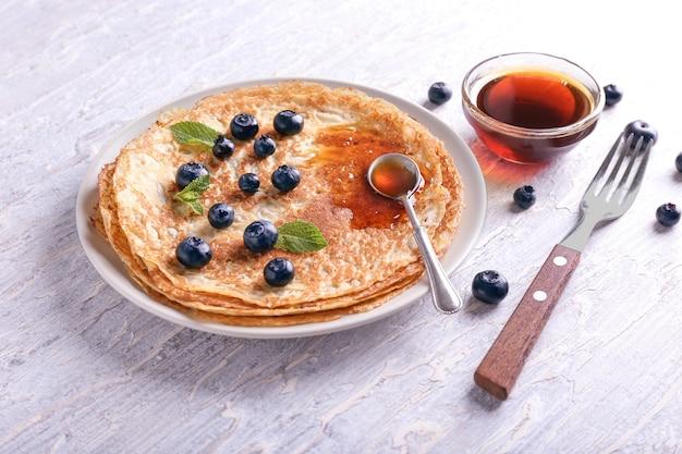 Piatto con deliziosi pancake sottili, frutti di bosco e sciroppo sul tavolo di legno