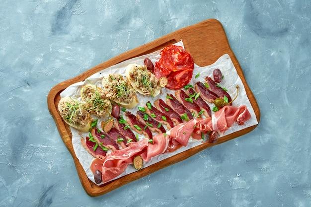 Piastra con diversi tipi di antipasti di carne - prosciutto affettato, chorizo, anatra essiccata e bruschetta con stufato su una tavola di legno.