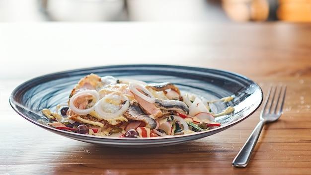 Piatto con insalata di pesce aringhe un tavolo in legno