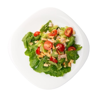 Piastra con insalata caesar fresca con pollo isolato su bianco