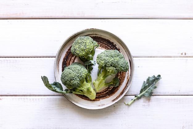 Piatto con broccoli verdi freschi, sparato da sopra su una struttura rustica di legno bianca