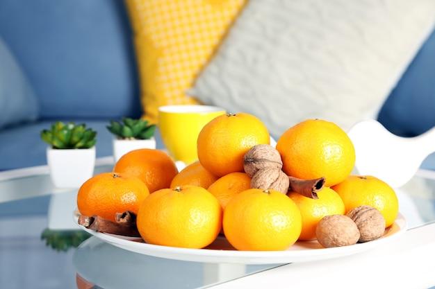 Piatto con mandarini freschi sul tavolo in soggiorno, primo piano