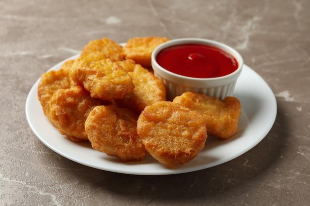 Piastra con pepite di pollo fritto e ketchup sul tavolo grigio, primi piani