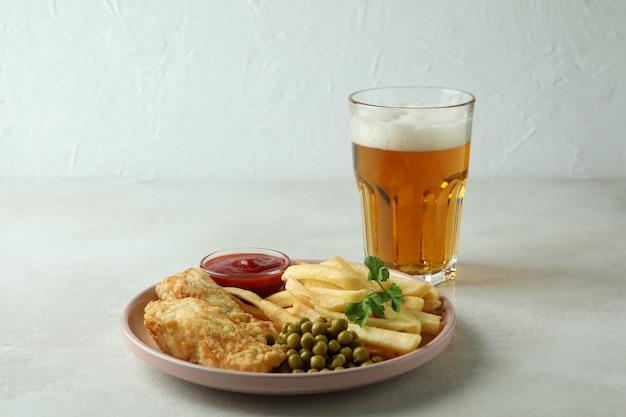 Piastra con pesce fritto e patatine fritte e birra sulla tavola strutturata bianca