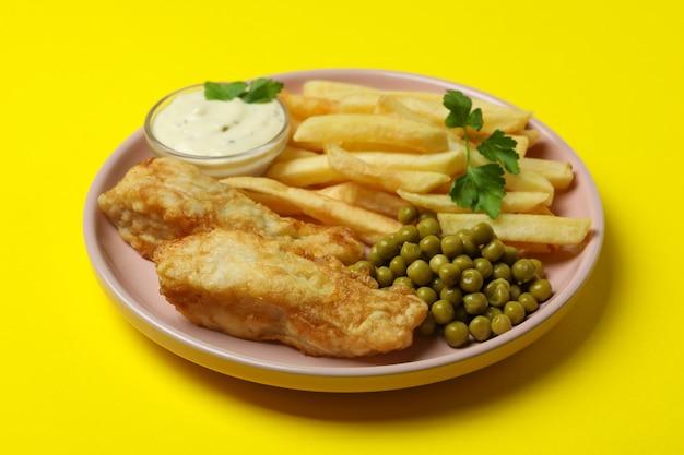Piastra con pesce fritto e patatine fritte isolato su giallo