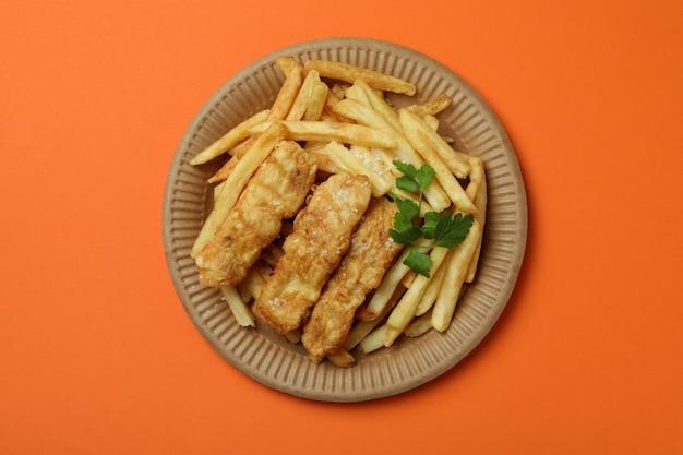 Piastra con pesce fritto e patatine fritte sull'arancia