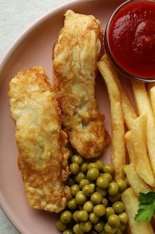 Piastra con pesce fritto e patatine fritte, piselli e ketchup, da vicino
