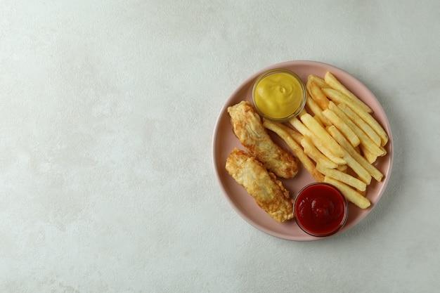Piastra con pesce fritto e patatine fritte e salse su bianco con texture