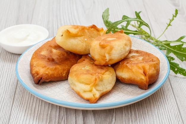 Piatto con torte fritte, ciotola con panna acida e verdure su tavole di legno grigie.