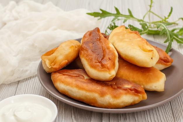 Piatto con torte fritte, ciotola con panna acida, pezzo di stoffa bianca e verdure su tavole di legno grigie.