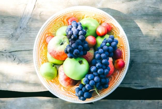Piatto con frutta sul ponte di legno. piatto rustico. concetto di stile di vita sano cibo vegetariano. vibrazioni estive. picnic vicino al fiume.