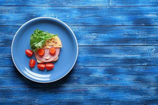Piatto con panino divertente su fondo di legno blu