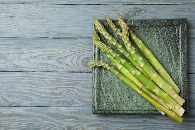 Piastra con asparagi verdi su fondo in legno