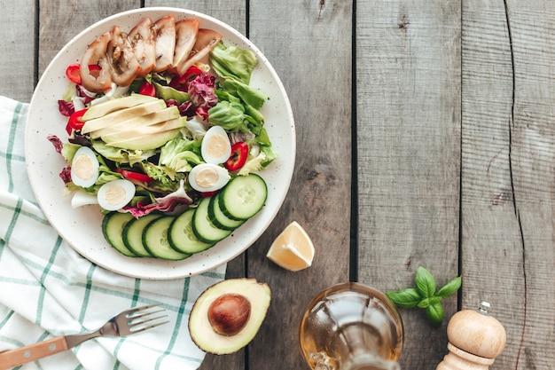 Piatto con foglie di insalata di lattuga verde, uovo di quaglia, avocado, pomodoro, cetriolo, pepe, basilico, olio d'oliva