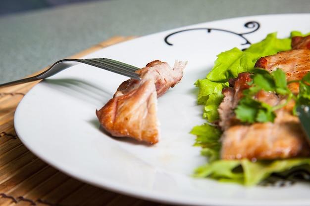 Piastra con carne alla griglia sul tavolo grigio