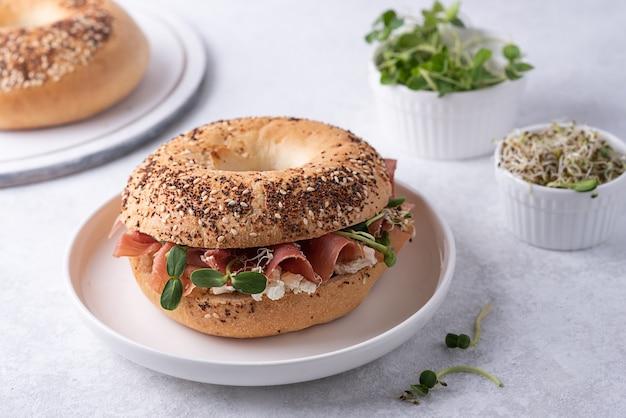 Piatto con bagel prosciutto e ricotta su sfondo bianco, panino con prosciutto e microgreens per colazione.