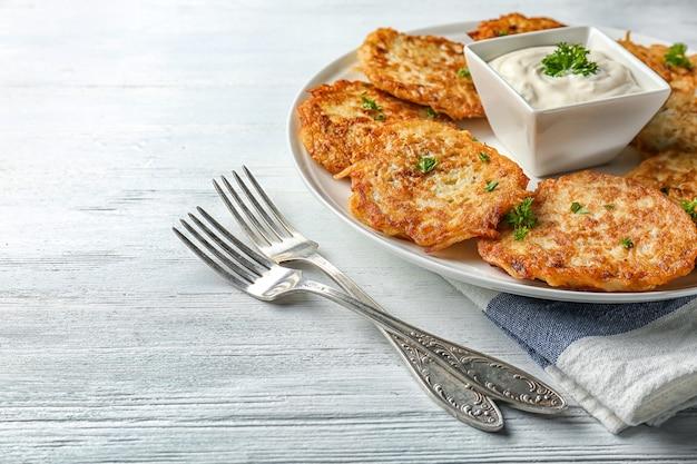 Piatto con frittelle di patate hanukkah e salsa sul tavolo