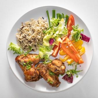 Piastra con cibo sano. riso selvatico, ali di pollo al forno e verdure varie in insalata.