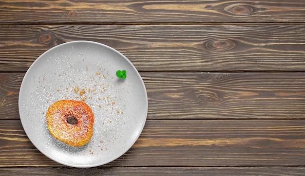 Un piatto con una ciambella fatta in casa con zucchero di canna e cosparso di zucchero a velo, decorato con una foglia di menta