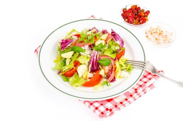 Piatto con lattuga, pomodori, olio d'oliva. menù vegetariano. foto in studio