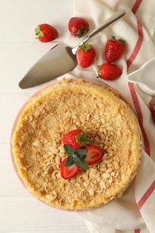 Piastra con torta napoleone con fragole su superficie di legno bianca