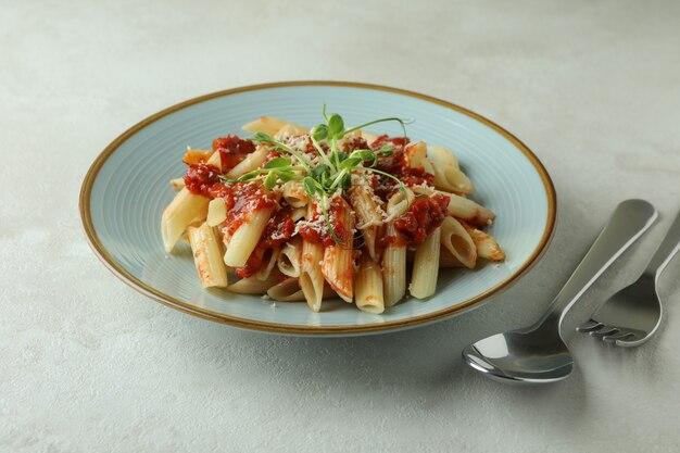 Piastra con pasta con salsa di pomodoro su bianco con texture