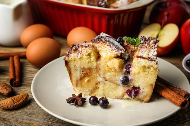 Piatto con un pezzo di budino di pane al forno su un tavolo di legno