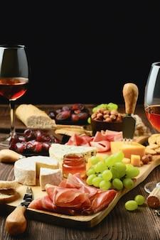 Piastra con prosciutto, uva, miele, datteri, cracker, noci e vino