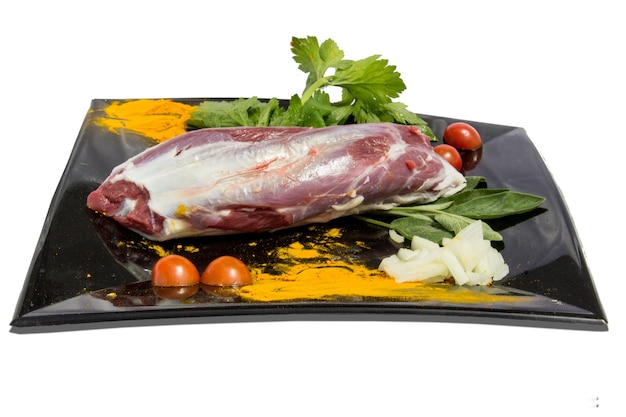 Piatto con carne cruda e decorazioni alimentari intorno su uno sfondo bianco, oggetto isolato