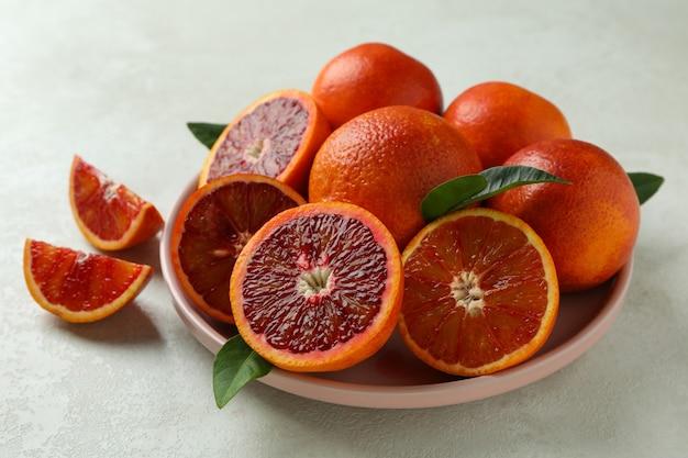 Piastra con arance rosse e foglie su bianco con texture