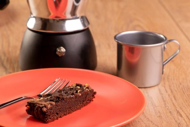 Piatto con una fetta di biscotto, una caffettiera e una tazza di caffè.